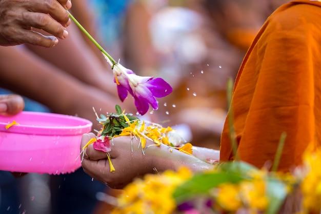 Strömendes wasser der leute zu den buddhistischen mönchen und gibt segen in thailand