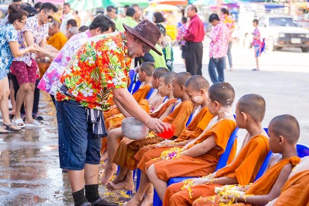 Strömendes wasser der leute zum buddhistischen anfänger und gibt segen in jährlichem festival thailands songkran im buddhistischen tempel