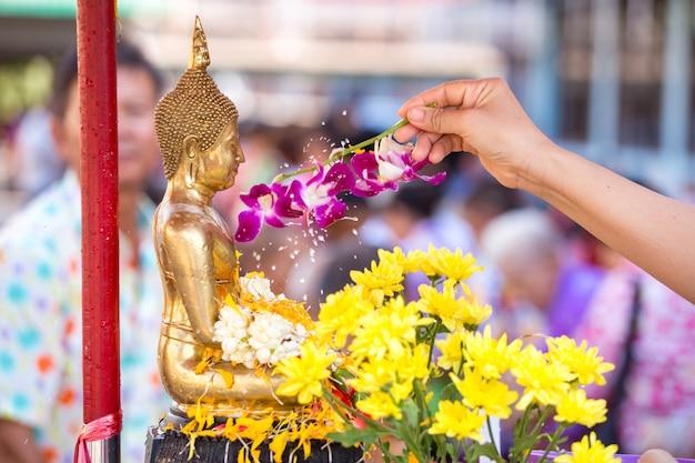 Strömendes wasser der leute zur buddhistischen statue und gibt segen in jährlichem festival thailands songkran im buddhistischen tempel