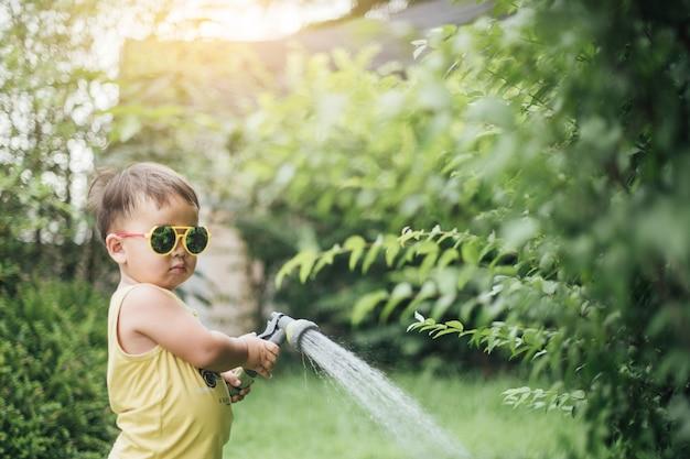 Strömendes wasser des asiatischen kleinen jungen auf den bäumen kind hilft, sich um die anlagen mit einer gießkanne im garten zu kümmern.