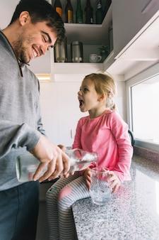 Strömendes wasser des glücklichen mannes im glas während mädchen, das auf küchenarbeitsplatte sitzt