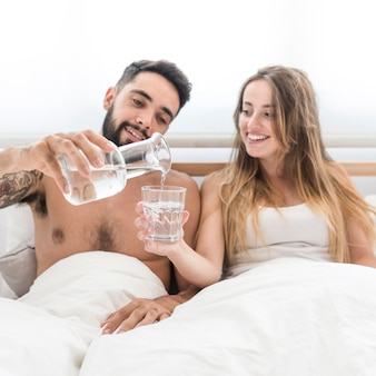 Strömendes wasser des mannes im glas für ihre freundin