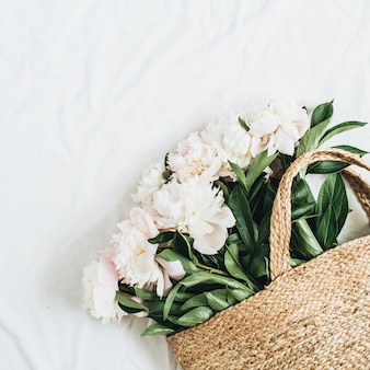 Strohbeutel mit weißen pfingstrosenblüten auf weißem hintergrund. flache lage, ansicht von oben