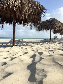Strohgedeckte sonnenschirme und sonnenliegen an einem verlassenen tropischen weißen sandstrand