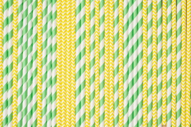 Strohhalme in grünem und gelbem farbhintergrund
