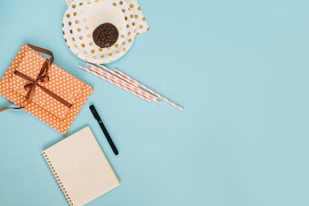 Strohhalme und geschenk zwischen muffin und notizbuch