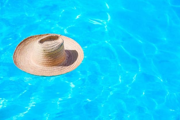Strohhut auf der oberfläche des blauen klaren swimmingpools