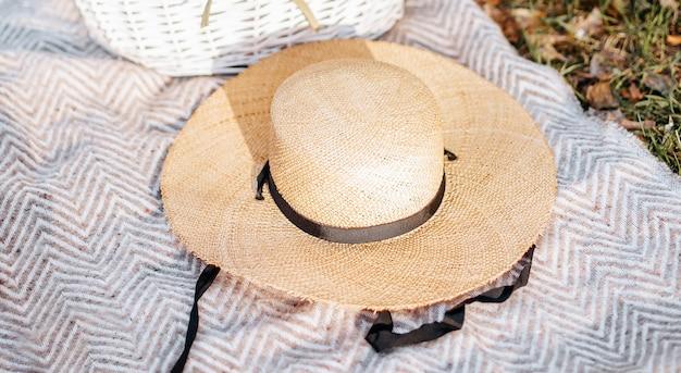 Strohhut auf einem plaid im garten im gras Premium Fotos