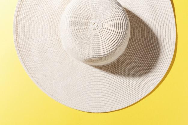 Strohhut auf hellem gelbem sonnigem hintergrund