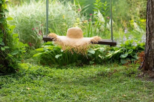 Strohhut auf schaukel auf natürlichem grün.