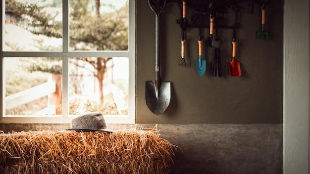 Strohhut auf stapel stroh mit dem gartenwerkzeug, das an der hallenwand hängt