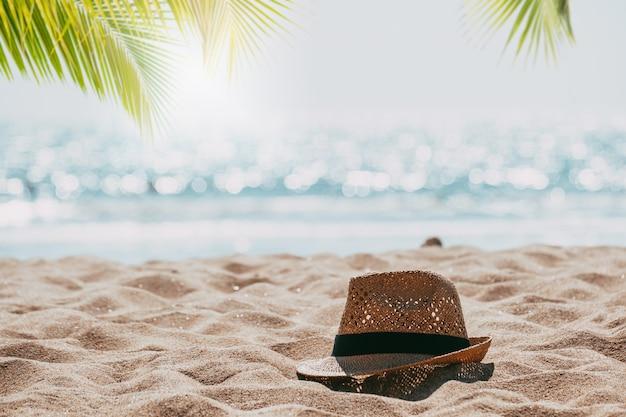 Strohhut auf tropischem strandmeer des sandes mit palme und unschärfe bokeh licht von ruhigem see