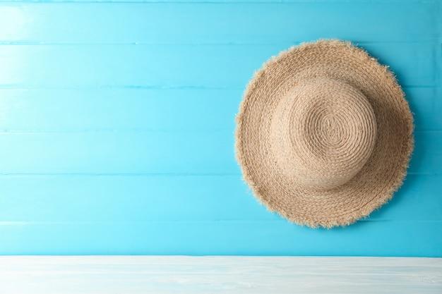 Strohhut auf weißem tisch gegen farbhintergrund, platz für text. sommerferienkonzept