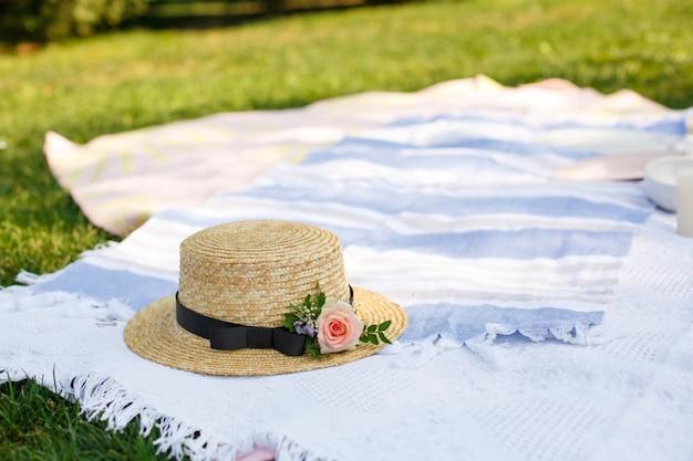 Strohhut mit frischen blumen lag auf einer weißen picknickdecke am hellen sommertag des grünen rasens