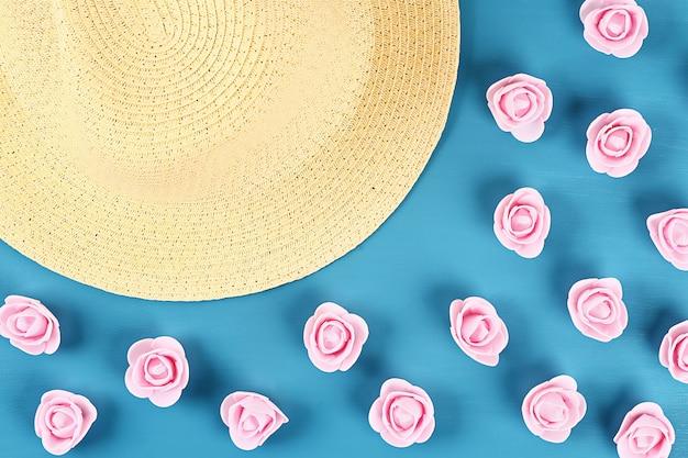 Strohhut mit kleinen rosen auf blauem hintergrund. ansicht von oben. sommer hintergrund. flach liegen.