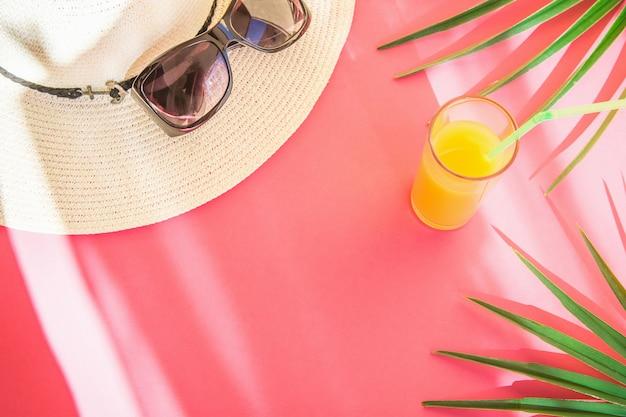 Strohhut-sonnenbrille-glas mit frischen tropischen fruchtsaft-palmblättern