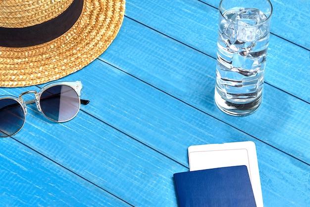 Strohhut, sonnenbrille, glas wasser mit eiswürfeln und reisepass mit ticket