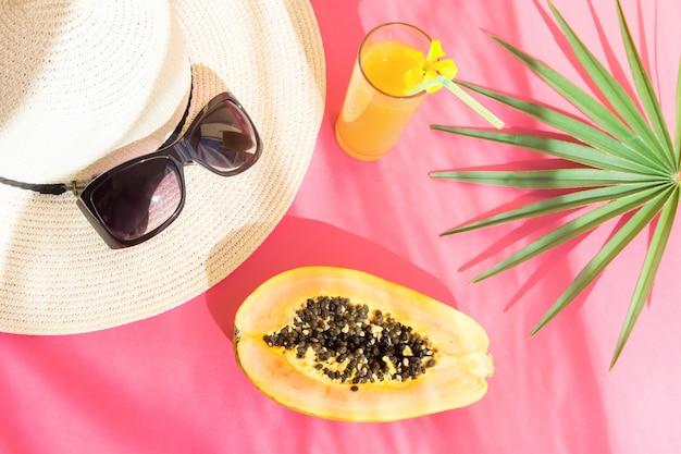 Strohhut-sonnenbrille-hohes glas mit tropischem fruchtsaft-papaya-palmblatt