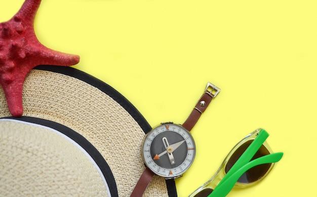 Strohhut, sonnenbrille, kompass und seestern auf gelb