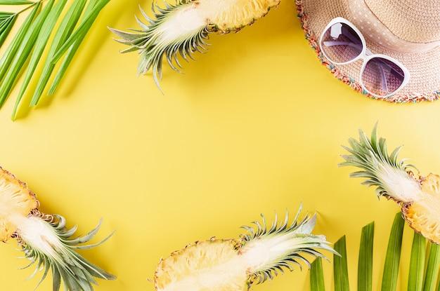 Strohhut, sonnenbrille, palmzweige und ananas auf gelbem papier