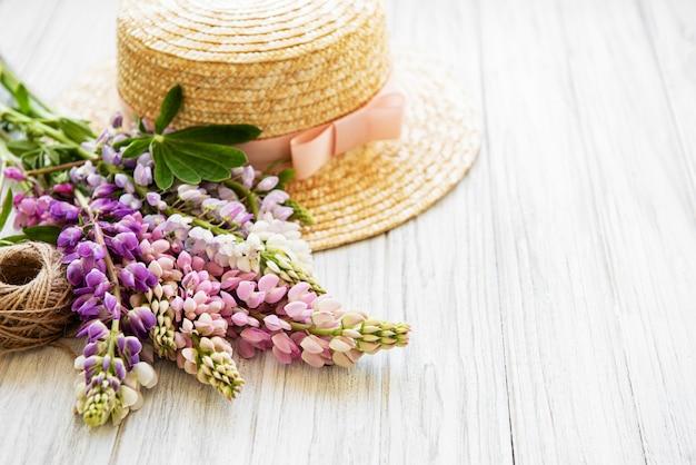 Strohhut und lupinenblüten