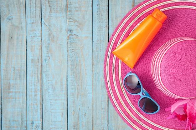 Strohhut und sonnenbrille auf blauem holz.