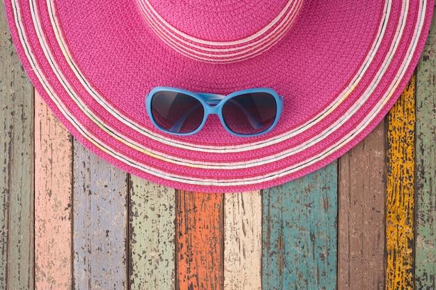 Strohhut und sonnenbrille auf vintage holz.