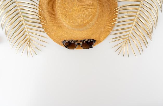 Strohhut und sonnenbrille draufsicht auf weißem hintergrund