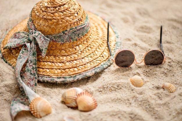Strohhut und sonnenbrille im sommerurlaub am sandstrand liegen gelassen