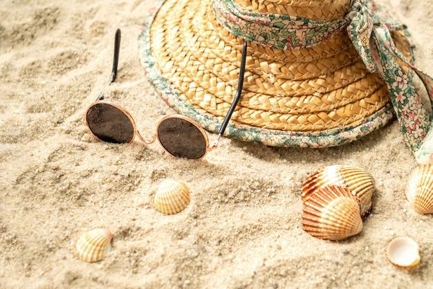 Strohhut und sonnenbrille liegen am strand zwischen muscheln sea