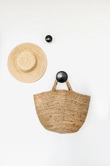 Strohhut und tasche auf leerem kleiderbügel