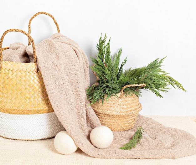 Strohkorb mit beiger weicher decke, nahaufnahme. stilvolle hygge umweltfreundliche wohnkultur artikel