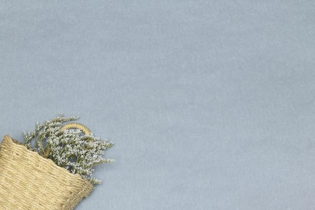 Strohkorb mit weißen blumen auf dem grauen papierhintergrund