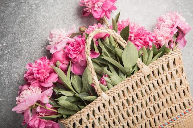 Strohsack mit rosa pfingstrosenblumen auf grauem hintergrund.