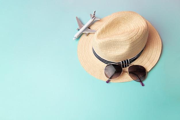 Strohstrandhut, sonnenbrille und weißes flugzeug im sommer