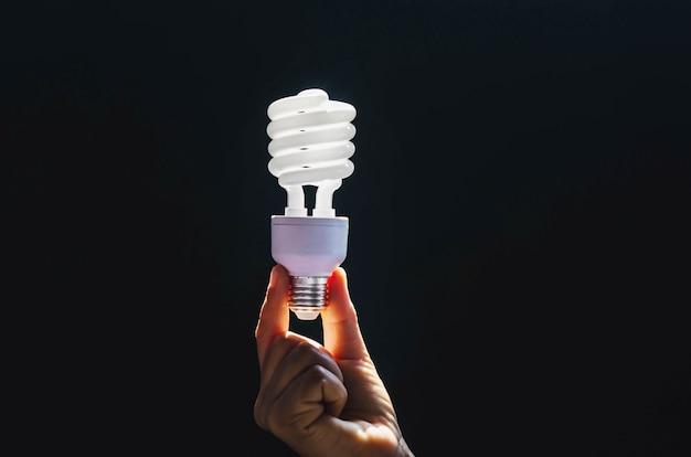 Strom- und energiekonzept - nah oben von der frauenhand, die leistungsfähige glühlampe hält