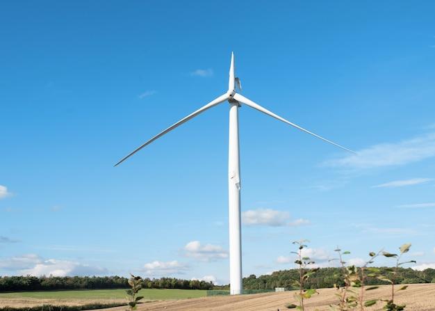 Strom-windkraftanlage mit gebrochener klinge und beschädigtem turm, der nach einem unfall auf reparatur wartet.
