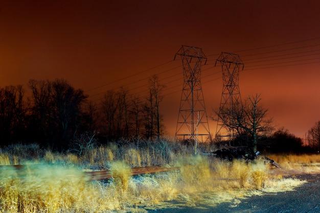 Stromkabelkommunikationstürme auf dem sonnenuntergangausdehnen