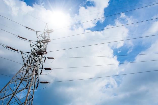 Stromleitung an der wolke des sonnigen tagesblauen himmels