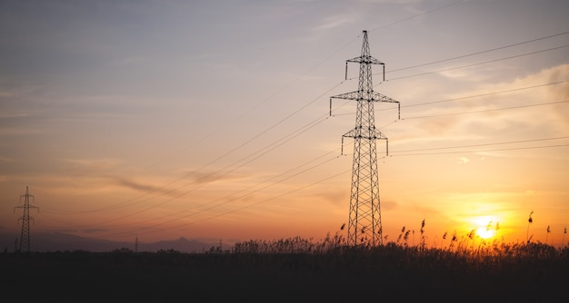 Stromleitung bei sonnenuntergang. hochspannungstürme