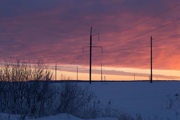 Stromleitung im frostigen wintersonnenuntergang