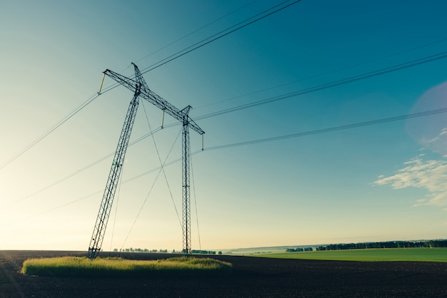 Stromleitungen auf blauem klarem himmel in der hintergrundbeleuchtung von der sonnenlichtnahaufnahme.