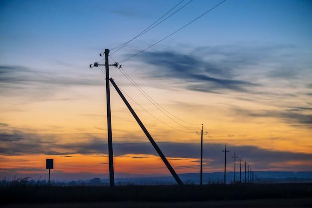 Stromleitungen auf dem gebiet auf sonnenaufganghintergrund.