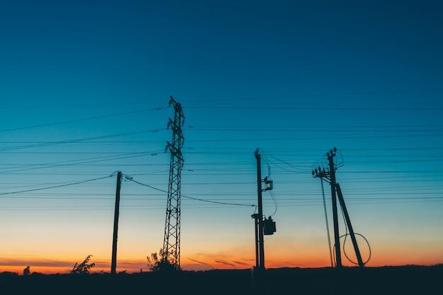 Stromleitungen auf dem gebiet im sonnenaufgang