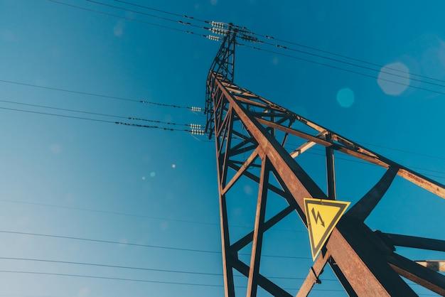 Stromleitungen des blauen himmels nahaufnahme. elektrische nabe an der stange. stromausrüstung mit kopierraum. hochspannungsdrähte am himmel. elektrizitätswirtschaft. turm mit blitzwarnschild.
