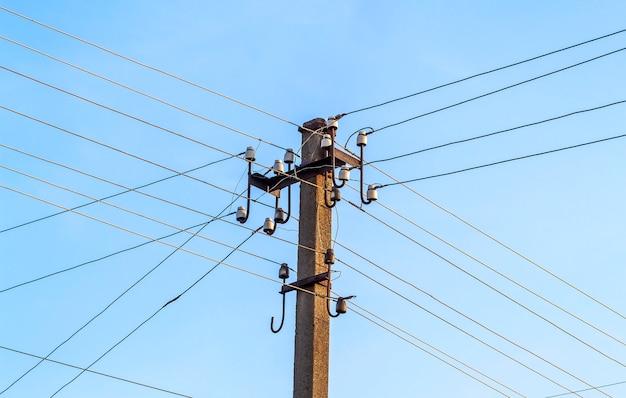 Stromleitungen und drähte des elektrischen pfostens mit blauem himmel