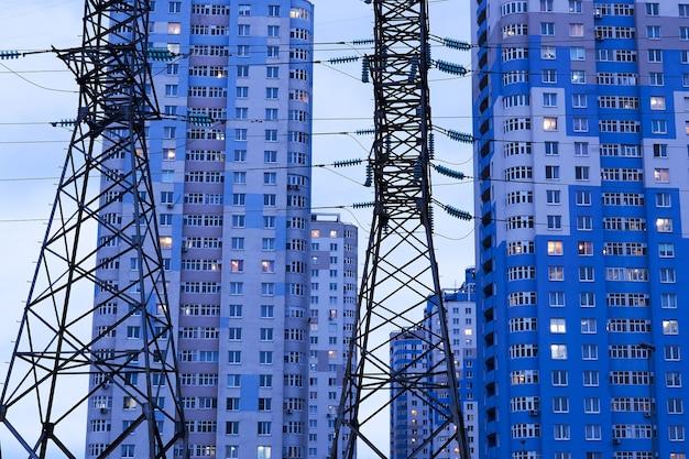Stromleitungsstützen vor dem hintergrund mehrstöckiger mehrfamilienhäuser in der abendbeleuchtung
