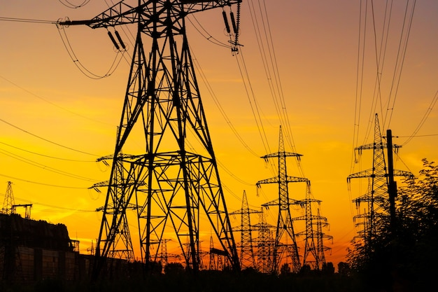 Strommasten, die die stromversorgung über eine ländliche landschaft während des sonnenuntergangs tragen