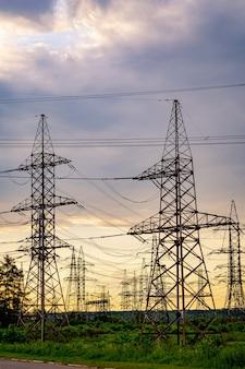 Strommasten tragen die stromversorgung über eine ländliche landschaft bei sonnenuntergang. selektiver fokus.