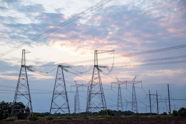 Strommasten und hochspannungsleitungen bei sonnenuntergang hintergrundgruppensilhouette der übertragung